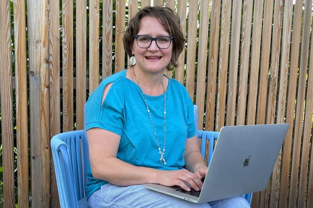 Jasmine Müller mit einem MacBook pro, lächelnd schreibend