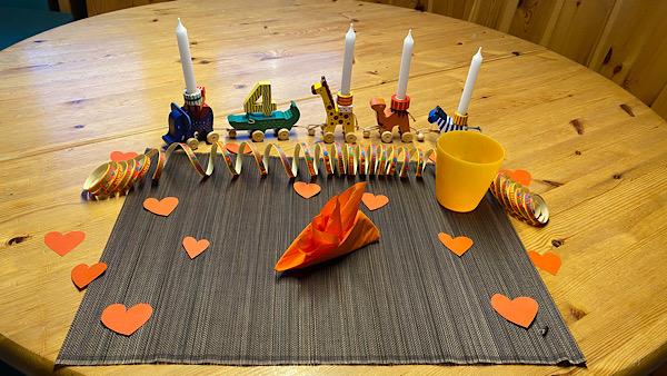 Ein festlich gedeckter Geburtstags-Frühstückstisch, mit einem Tier-Zug, auf dem 4 Kerzen eingesteckt sind.