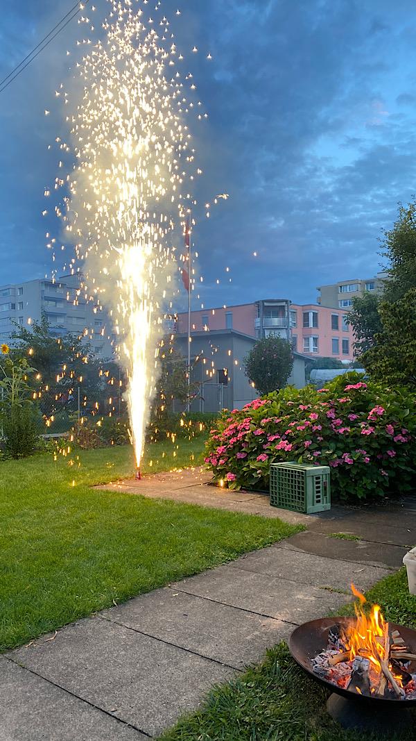 Ein Zuckerstock ist angezündet in einem Garten und neben an brennt ein kleines Feuer in der Feuerschale.