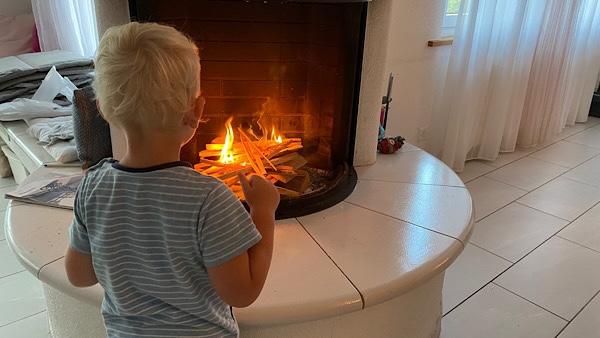 Mein Sohn steht vor dem offenen Kaminfeuer und bestaunt das brennende Feuer.