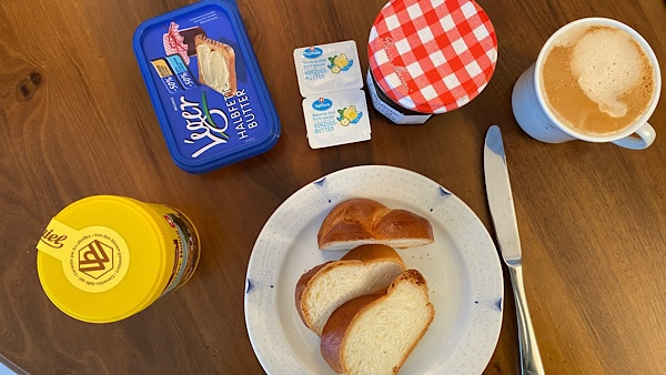 Ein gedeckter Tisch mit einem Teller, darauf drei Stück Zopf. Dazu Honig, Butter, Konfitüre und eine Tasse Kaffee.