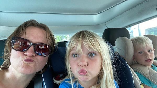 Meine Tochter, mein Sohn und ich auf der Rückbank im VW Bus machen ein Kussmund.