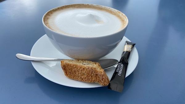 Eine Tasse Cappuccino mit einem Cantuccini und einem Säcklein Zucker.